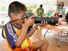 Photographer teaches youngsters how to hold a big camera and take photos of new friends - Ban Muang Refugee Camp