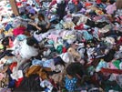 Women sort through tons of clothing donated to the Ban Muang refugee camp